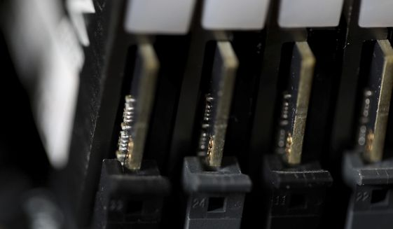 This Feb 23, 2019, file photo shows the inside of a computer in Jersey City, N.J. Cybersecurity teams worked feverishly Sunday, July 4, 2021, to stem the impact of the single biggest global ransomware attack on record, with some details emerging about how the Russia-linked gang responsible breached the company whose software was the conduit. An affiliate of the notorious REvil gang, infected thousands of victims in at least 17 countries on Friday, largely through firms that remotely manage IT infrastructure for multiple customers, cybersecurity researchers said. (AP Photo/Jenny Kane, File)