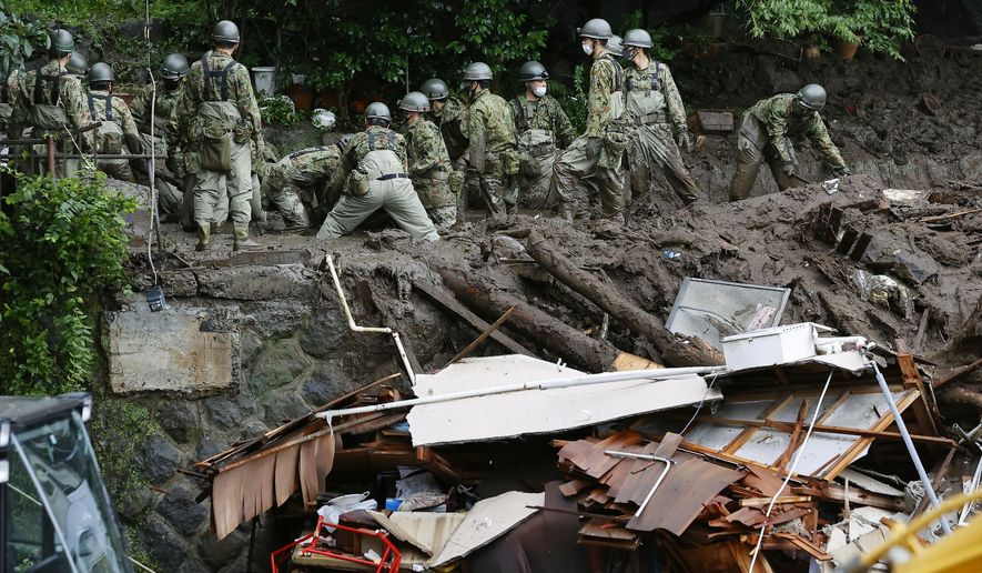 Rescuers continue a search operation at the site of a mudslide at Izusan in Atami, Shizuoka prefecture, southwest of Tokyo Monday, July 5, 2021. (Kyodo News via AP)