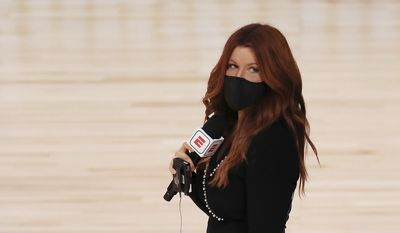 ESPN reporter Rachel Nichols stands on the court before an NBA basketball game between the Houston Rockets and the Dallas Mavericks, Friday, July 31, 2020, in Lake Buena Vista, Fla. (Mike Ehrmann/Pool Photo via AP)