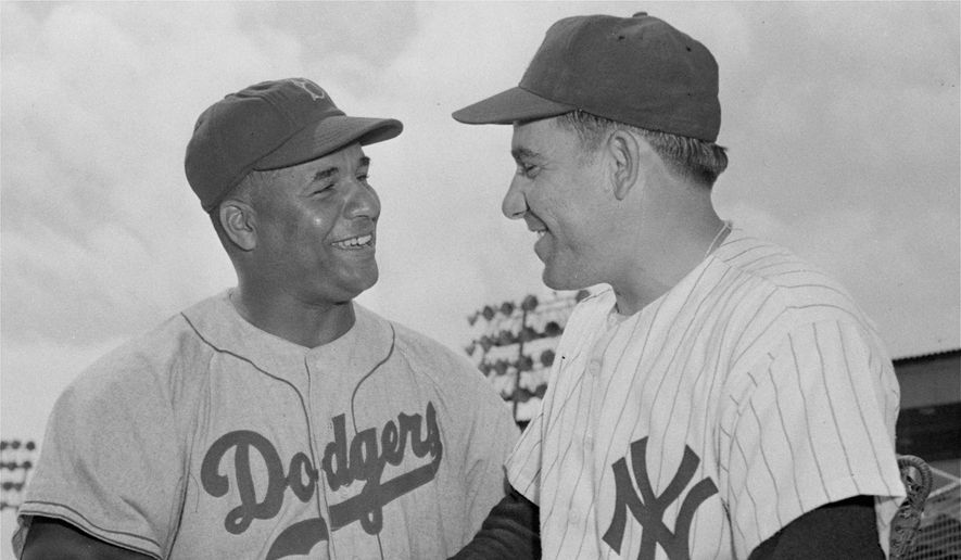 Brooklyn Dodgers' Roy Campanella, left, and New York Yankees' Yogi Berra, rival catchers, exchanged greetings before an exhibition game on March 25, 1955.(AP Photo) **FILE**
