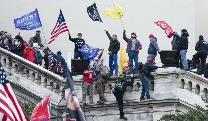 Rioters stand on stairs to a balcony on the West Front of the U.S. Capitol on Jan. 6, 2021, in Washington. (AP Photo/Jose Luis Magana)