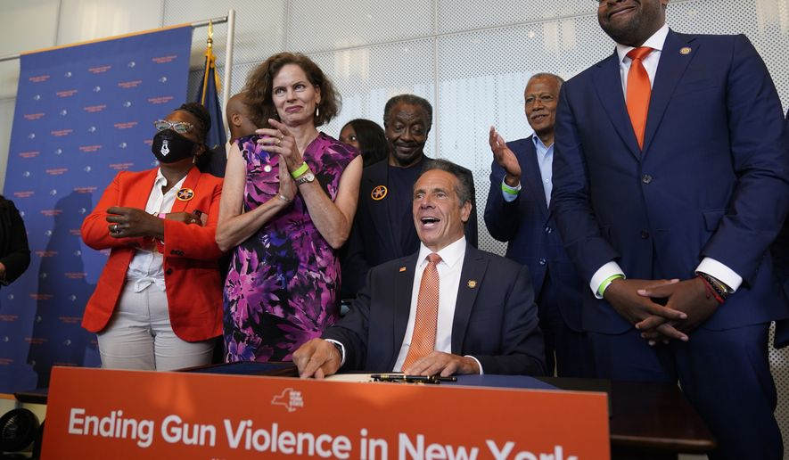 Surrounded by supporters and advocates, New York Governor Andrew Cuomo, center, signs legislation on gun control in New York, Tuesday, July 6, 2021. Cuomo signed two pieces of legislation to combat gun violence in New York state. (AP Photo/Seth Wenig)