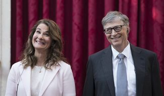 FILE - In this April 21, 2017, file photo, Philanthropist and co-founder of Microsoft, Bill Gates, right, and his wife Melinda react, prior to being awarded the Legion of Honour at the Elysee Palace in Paris.   Bill Gates and Melinda French Gates will continue to work together as co-chairs of their foundation even after their planned divorce. However, if after two years they cannot continue in their roles, French Gates will resign her positions as co-chair and trustee, The Bill and Gates Melinda Foundation announced Wednesday, July 7, 2021.  (AP Photo/Kamil Zihnioglu, Pool)