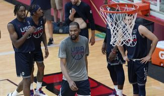 Kevin Durant, center, prepares for a drill with teammates during practice for USA Basketball, Wednesday, July 7, 2021, in Las Vegas. (AP Photo/John Locher)