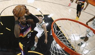 Phoenix Suns' Deandre Ayton (22) attempts a shot ahead of Milwaukee Bucks' Brook Lopez (11) during the first half of Game 1 of basketball's NBA Finals, Tuesday, July 6, 2021, in Phoenix. (Christian Petersen/Pool Photo via AP) **FILE**