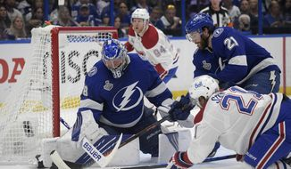 Montreal Canadiens center Eric Staal (21) and Tampa Bay Lightning center Brayden Point (21) reach for the puck next to Lightning goaltender Andrei Vasilevskiy (88) during the first period in Game 5 of the NHL hockey Stanley Cup finals, Wednesday, July 7, 2021, in Tampa, Fla. (AP Photo/Phelan Ebenhack)