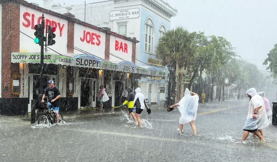 Determined visitors head for Sloppy Joe's Bar while crossing a flooded Duval Street as heavy winds and rain pass over Key West, Fla., Tuesday, July 6, 2021. The weather was getting worse in southern Florida on Tuesday morning as Tropical Storm Elsa began lashing the Florida Keys, complicating the search for survivors in the condo collapse and prompting a hurricane watch for the peninsula's upper Gulf Coast. (Rob O'Neal/The Key West Citizen via AP)