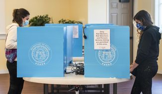 In this Jan. 5, 2021, file photo, Emily Murdock, left, and her twin sister Elizabeth Murdock vote in Georgia's U.S. Senate runoff election in Evans, Ga. (Michael Holahan/The Augusta Chronicle via AP) ** FILE **