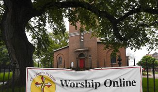 A sign hangs on the fence of St. Anne's Episcopal Church in Annapolis, Md., displaying information for online services, Friday, May 22, 2020. (AP Photo/Susan Walsh)