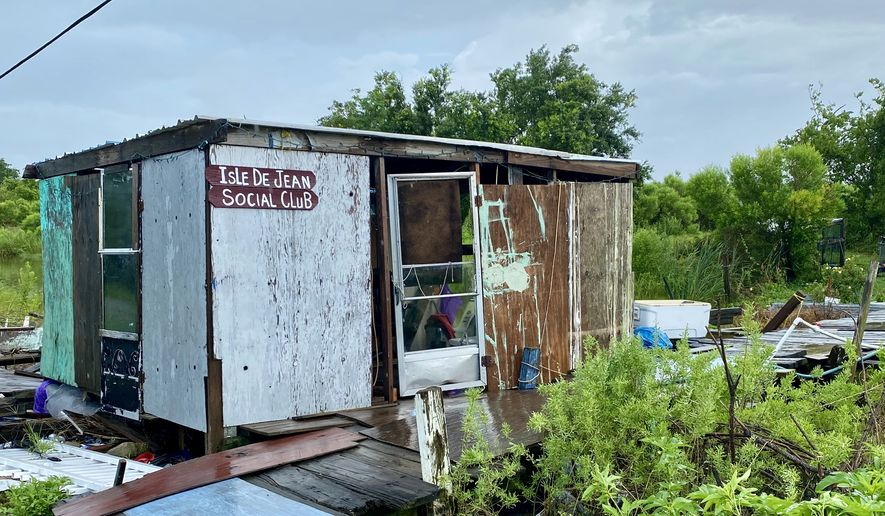 The ramshackle Isle de Jean Charles Social Club is intended as a joke by one of the Louisiana island's three dozen residents, who are to be resettled by the state government via a $50 million project. The island is slowly disappearing in the Gulf of Mexico. (James Varney/The Washington Times)
