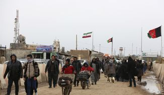 FILE- In this Feb. 20, 2019 file photo, Afghans return to Afghanistan at the Islam Qala border with Iran, in the western Herat Province. Taliban have taken control of Islam Qala crossing border in western Herat province at the neighboring Iran, an Afghan official and Iranian media confirmed on Thursday, July 8, 2021.  (AP Photo/Rahmat Gul, File)