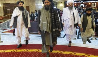 FILE  - In this file photo taken on Thursday, March 18, 2021, Taliban co-founder Mullah Abdul Ghani Baradar, center, arrives with other members of the Taliban delegation for an international peace conference in Moscow, Russia. A delegation of the Taliban visited Moscow on Thursday, July 8, 2021 to offer assurances that their quick gains in Afghanistan don't threaten Russia or its allies in Central Asia. (AP Photo/Alexander Zemlianichenko, Pool, File)