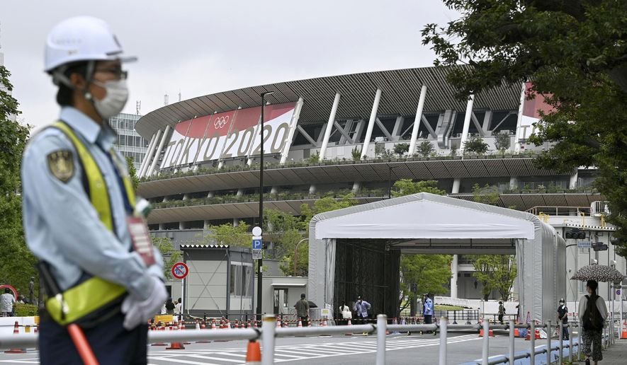 A security guard wearing face masks guards outside the National Stadium in Tokyo, Thursday, July 8, 2021. Japan is set to place Tokyo under a state of emergency starting next week and lasting through the Olympics, with COVID-19 cases surging and feared to multiply during the Games. (Shinji Kita/Kyodo News via AP)