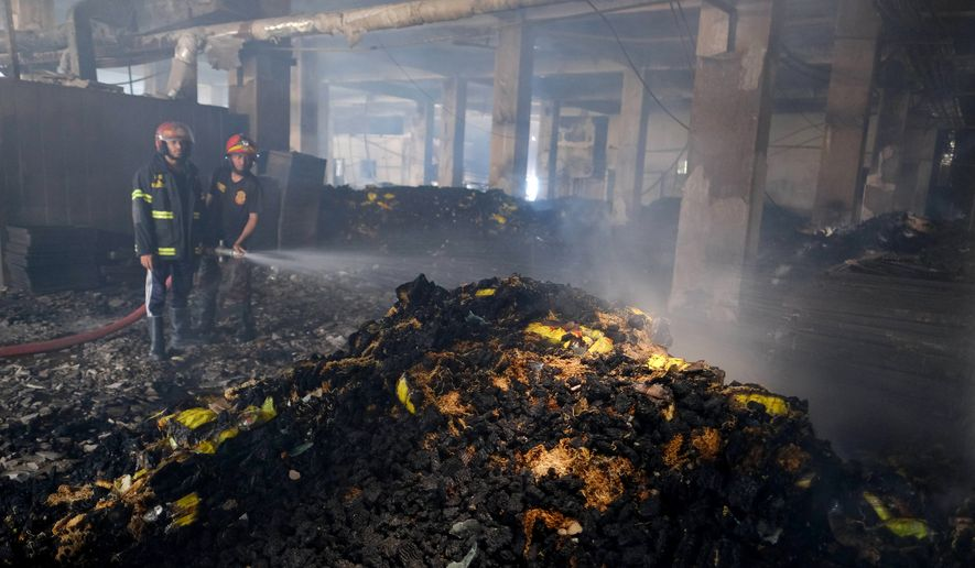 Firefighters work to douse a fire inside a food and beverage factory in Rupganj, outside Dhaka, Bangladesh, Friday, July 9, 2021. At least 52 people died in a huge blaze that engulfed a food and beverage factory outside Bangladesh's capital, fire officials said Friday, in the latest industrial disaster to hit the South Asian nation. (AP Photo/Mahmud Hossain Opu)