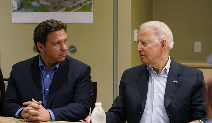 In this July 1, 2021, file photo President Joe Biden, right, looks at Florida Gov. Ron DeSantis, left, during a briefing with first responders and local officials in Miami on the condo tower that collapsed in Surfside, Fla. As he prepares for a reelection bid next year that could propel him into a presidential campaign, the tragedy in Surfside is exposing voters to a different side of DeSantis. (AP Photo/Susan Walsh, File)