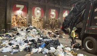 A worker unloads a garbage truck at ecomaine, Tuesday, June 22, 2021, in Portland, Maine. Waste-to-energy converters like ecomaine are seeing an uptick in the amount of trash they collect to produce power as the coronavirus pandemic winds down in the U.S. These facilities burn garbage to create electricity. Environmentalists and renewable energy advocates are debating whether creating more energy by burning the excess waste is a safe idea. (AP Photo/Patrick Whittle)