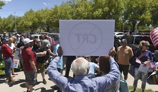 In this May 25, 2021, file photo, a man holds up a sign against Critical Race Theory during a protest outside a Washoe County School District board meeting in Reno, Nev. (Andy Barron/Reno Gazette-Journal via AP, File)  **FILE**
