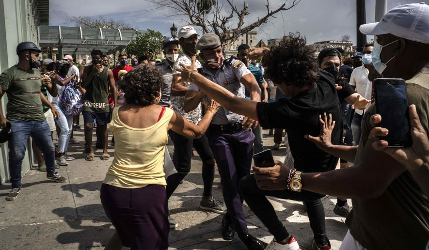 Police scuffle and detain an anti-government demonstrator during a protest in Havana, Cuba, Sunday, July 11, 2021. Hundreds of demonstrators went out to the streets in several cities in Cuba to protest against ongoing food shortages and high prices of foodstuffs, amid the new coronavirus crisis. (AP Photo/Ramon Espinosa)