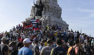 Anti-government protesters gather at the Maximo Gomez monument in Havana, Cuba, Sunday, July 11, 2021. Hundreds of demonstrators took to the streets in several cities in Cuba to protest against ongoing food shortages and high prices of foodstuffs. (AP Photo/Eliana Aponte)