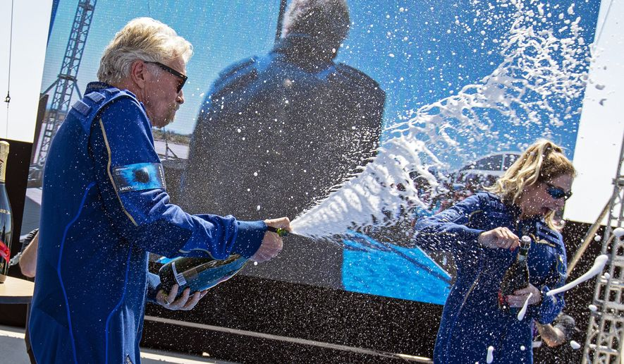 Virgin Galactic founder Richard Branson, left, sprays champagne to crew member Beth Moses while celebrating their flight to space from Spaceport America near Truth or Consequences, N.M., Sunday, July 11, 2021. (AP Photo/Andres Leighton)