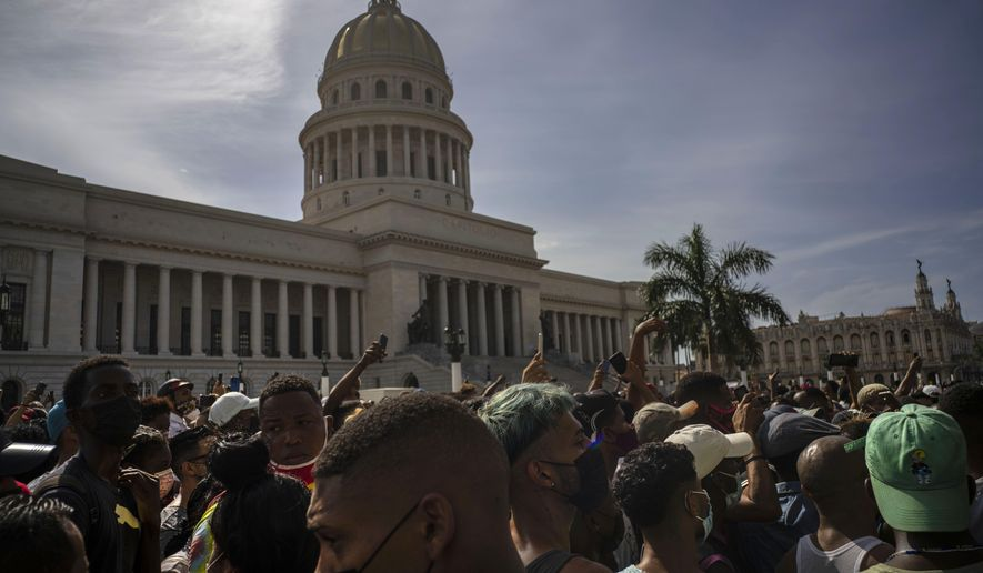 People protest in front of the Capitol in Havana, Cuba, Sunday, July 11, 2021. Hundreds of demonstrators went out to the streets in several cities in Cuba to protest against ongoing food shortages and high prices of foodstuffs, amid the new coronavirus crisis. (AP Photo/Ramon Espinosa)