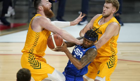 United States' Bradley Beal drives into Australia's Aron Baynes, left, and Jock Landale, right, during an exhibition basketball game Monday, July 12, 2021, in Las Vegas. (AP Photo/John Locher)
