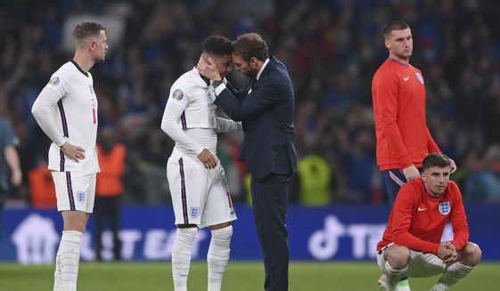 England's manager Gareth Southgate, center right, consoles England's Jadon Sancho after the penalty shootout of the Euro 2020 soccer final match between England and Italy at Wembley stadium in London, Sunday, July 11, 2021. (Laurence Griffiths/Pool via AP)