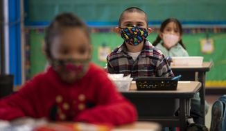 In this April 13, 2021, file photo, kindergarten students sit in their classroom on the first day of in-person learning at Maurice Sendak Elementary School in Los Angeles. California health officials announced new coronavirus rules for public schools on Monday, July 12, 2021. The new rules eliminate physical distancing while making sure no one will miss class time even if they are exposed to someone with the virus. But the state would continue to require all students and staff to wear masks indoors. (AP Photo/Jae C. Hong, File)