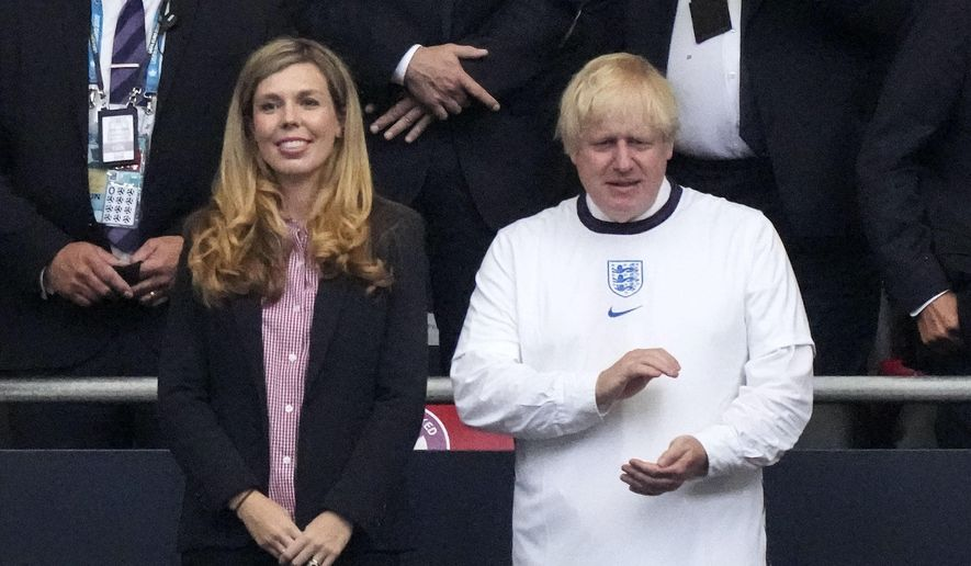 British Prime Minister Boris Johnson claps hands on the tribune beside his wife Carrie prior the Euro 2020 soccer championship final between England and Italy at Wembley stadium in London, Sunday, July 11, 2021. (AP Photo/Frank Augstein, Pool)