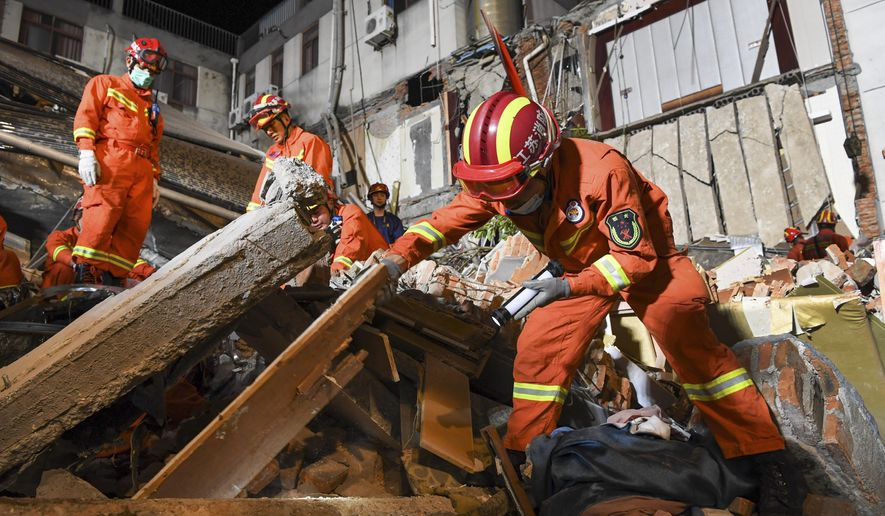 In this photo released by Xinhua News Agency, rescuers search for survivors at a collapsed hotel in Suzhou in eastern China's Jiangsu Province, Monday, July 12, 2021. The hotel building collapsed Monday afternoon. (Li Bo/Xinhua via AP)