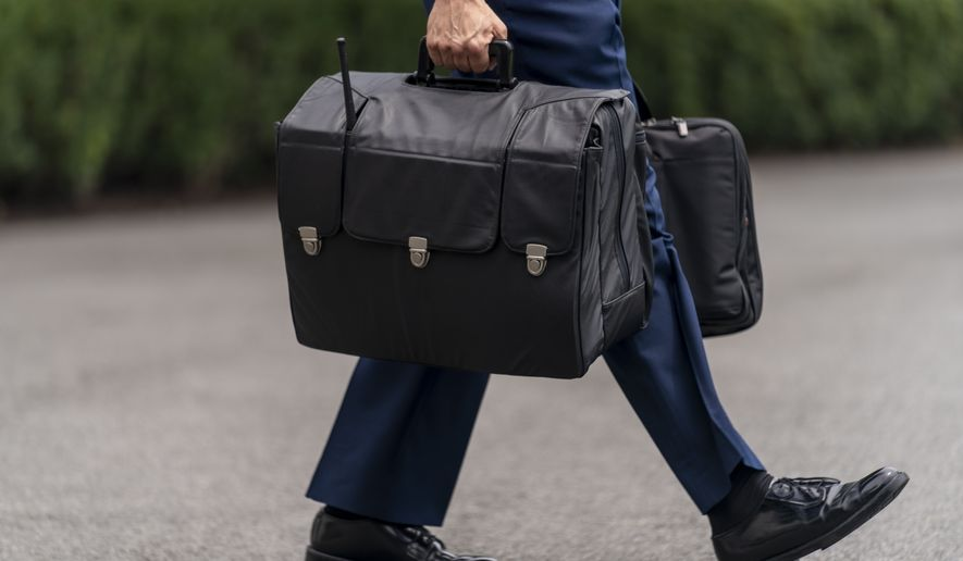 """A U.S. military aide carries the """"President's emergency satchel,"""" also know as """"the football,"""" with the nuclear launch codes, walks towards Marine One on the South Lawn of the White House in Washington, Tuesday, July 13, 2021, to join President Joe Biden for a short trip to Andrews Air Force Base, Md., and then on to Philadelphia. (AP Photo/Andrew Harnik)"""