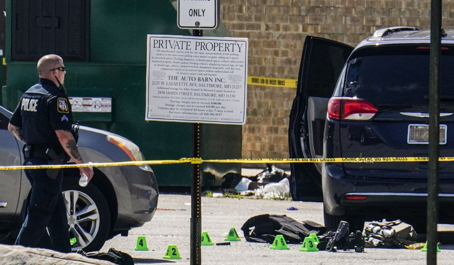 Body armor is seen near a minivan in a parking lot area of a mall where two officers on the U.S. Marshals' task force where allegedly shot in Baltimore, according to officials, Tuesday, July 13, 2021. The Marshal's wounds aren't thought to be life-threatening. (AP Photo/Julio Cortez)
