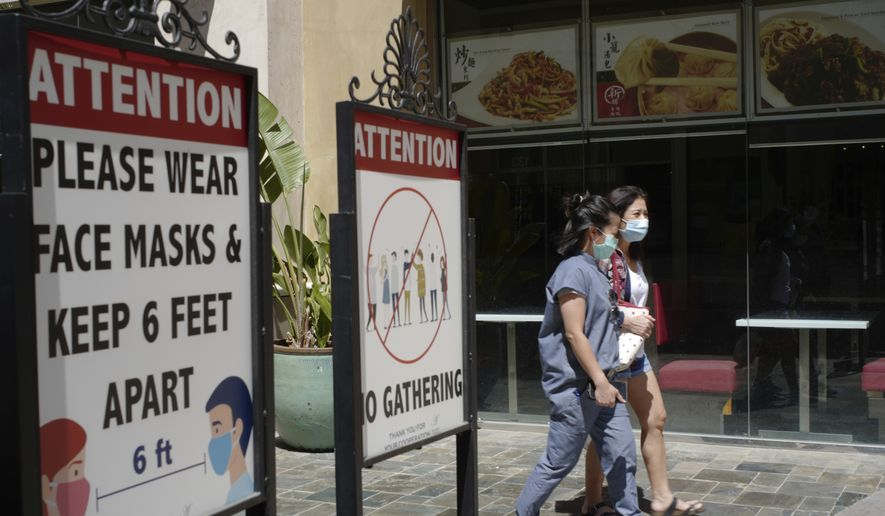 Customers wear face masks in an outdoor mall with closed business amid the COVID-19 pandemic in Los Angeles. Coronavirus cases have jumped 500% in Los Angeles County over the past month and health officials warned Tuesday, July 13, 2021, that the especially contagious delta variant of the disease continues to spread rapidly among California's unvaccinated population. (AP Photo/Damian Dovarganes,File)