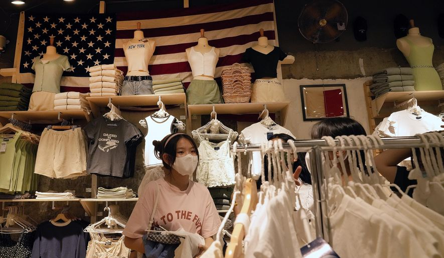 """Women wearing face masks shop at an American fashion boutique in Beijing on Sunday, July 11, 2021. China on Tuesday, July 13, denounced an appeal by Treasury Secretary Janet Yellen for a U.S.-European """"unified front"""" against Chinese """"unfair economic practices"""" and human rights abuses. (AP Photo/Andy Wong)"""