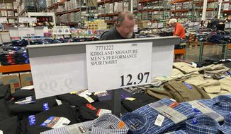 A sign displays the price for shirts as a shopper peruses the offerings at a Costco warehouse on Thursday, June 17, 2021, in Lone Tree, Colo. American consumers faced a third straight monthly surge in princes in June, the latest sign that a rapid reopening of the economy is fueling a pent-up demand for goods and services that in many cases remain in short supply.  (AP Photo/David Zalubowski)