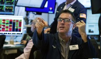 Trader Richard Brophy works on the floor of the New York Stock Exchange, Tuesday, July 13, 2021. Stocks wobbled between small gains and losses in early trading Tuesday as investors weigh the latest quarterly earnings reports from big U.S. companies and concerns about inflation. (AP Photo/Richard Drew)