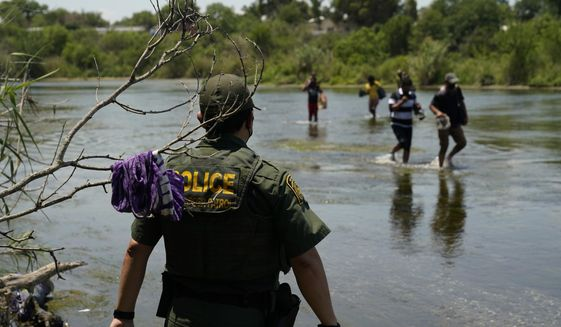 In this June 15, 2021, photo, a Border Patrol agent watches as a group of migrants walk across the Rio Grande on their way to turning themselves in upon crossing the U.S.-Mexico border in Del Rio, Texas. (AP Photo/Eric Gay) ** FILE **