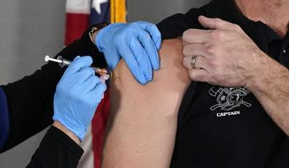 In this Wednesday, Dec. 16, 2020, file photo, the Pfizer vaccine for COVID-19 is administered at the Arizona Department of Health Services State Laboratory in Phoenix. On Friday, July 9, 2021, Arizona reported 921 additional confirmed COVID-19 cases, the biggest daily increase in two months, as the coronavirus continued to spread among unvaccinated people. (AP Photo/Ross D. Franklin, File)