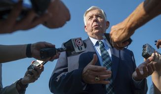 Missouri Gov. Mike Parson answers media's questions after he signed a bill to increase the state's gas tax on Tuesday, July 13, 2021, at the Buck O'Neil Bridge in Kansas City, Mo. It's the first gas tax increase for Missourians in decades. (Shelly Yang/The Kansas City Star via AP)