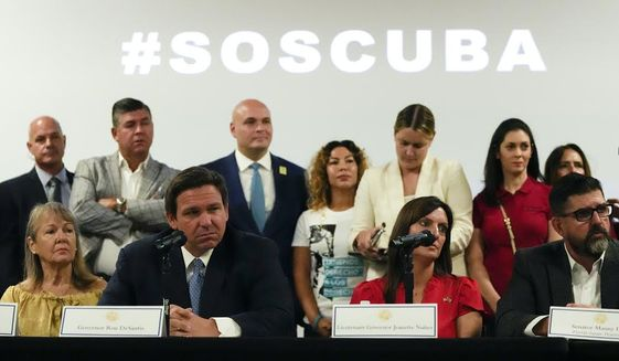 Florida Gov. Ron DeSantis, seated at left, discusses the situation in Cuba at the American Museum of the Cuban Diaspora in Miami. (AP Photo/Rebecca Blackwell)