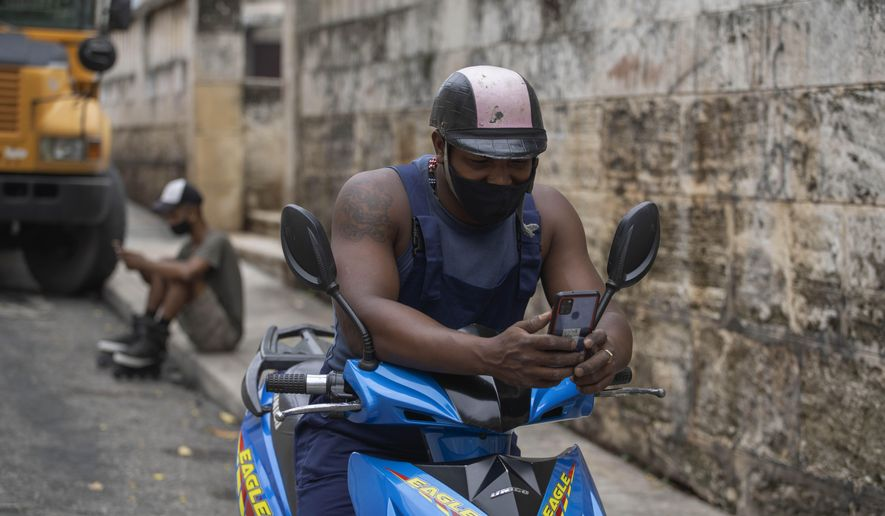 Men use a prepaid public Wi-FI connection on their cellphones next to a park that's popular for connectivity, which costs money, in Havana, Cuba, Tuesday, July 14, 2021. The government responded to Sunday's anti-government protests by shutting down internet and mobile data services by the state-run phone monopoly, effectively cutting off social media. (AP Photo/Eliana Aponte) **FILE**