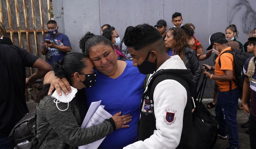 Lizeth Morales, left, of Honduras, and her son, Alex Cortillo, right, get a hug from Erika Valladares Ponce, center, as they wait to cross into the United States to begin the asylum process Monday, July 5, 2021, in Tijuana, Mexico. Dozens of people are allowed into the U.S. twice a day at a San Diego border crossing, part of a system that the Biden administration cobbled together to start opening back up the asylum system in the U.S. Immigration advocates have been tasked with choosing which migrants can apply for a limited number of slots to claim humanitarian protection. (AP Photo/Gregory Bull)