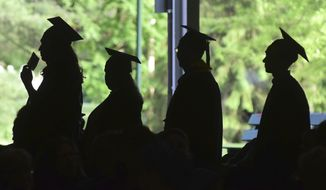 FILE - In this Friday, June 1, 2018,, file photo, graduates are silhouetted against the green landscape as they line up to receive their diplomas at Berkshire Community College's commencement exercises at the Shed at Tanglewood in Lenox, Mass. Critics of traditional four-year degree programs say grads leave burdened with student loans and no clear path to a career. But experts say the four-year degree is still a good investment since it leads to higher overall lifetime earnings compared to workers without a degree. (Gillian Jones/The Berkshire Eagle via AP, File)