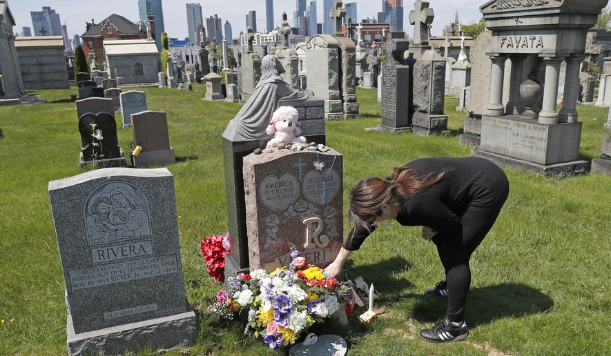 In this Sunday, May 10, 2020, file photo, Sharon Rivera adjusts flowers and other items left at the grave of her daughter, Victoria, at Calvary Cemetery in New York, on Mother's Day. Victoria died of a drug overdose on Sept. 22, 2019, when she just 21 years old. According to a report released by the Centers for Disease Control and Prevention on Wednesday, July 14, 2021, drug overdose deaths soared to a record 93,000 last year in the midst of the COVID-19 pandemic. (AP Photo/Kathy Willens, File)
