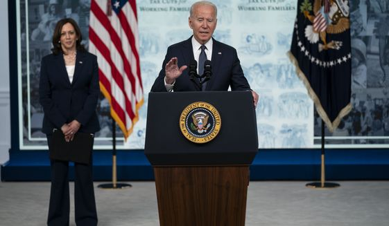 Vice President Kamala Harris listens as President Joe Biden speaks during an event to mark the start of monthly Child Tax Credit relief payments, in the South Court Auditorium on the White House complex, Thursday, July 15, 2021, in Washington. (AP Photo/Evan Vucci)