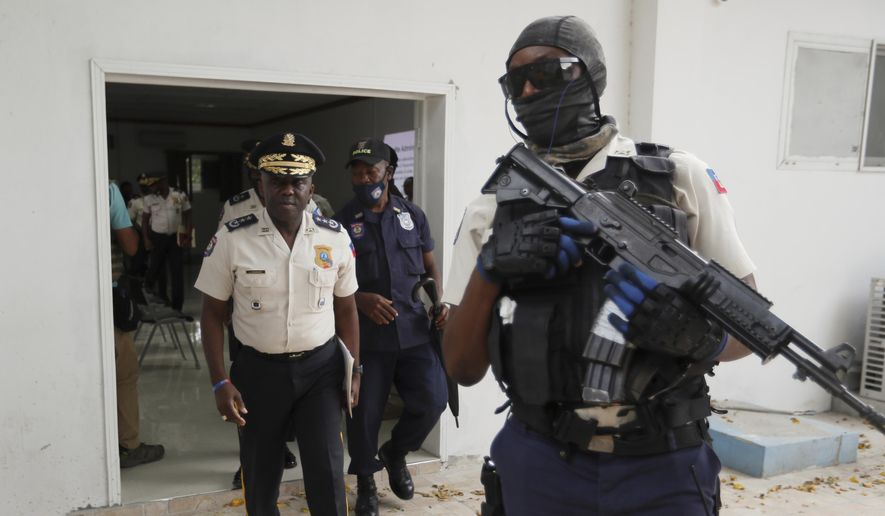 Leon Charles, left, head of Haiti's National Police, leaves a room after a news conference at police headquarters in Port-au-Prince, Wednesday, July 14, 2021. Charles gave an update on the investigation of the July 7 assassination of President Jovenel Moise. (AP Photo/Fernando Llano)