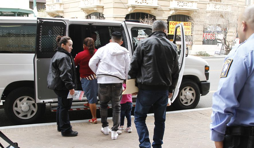 In this Feb. 28, 2020, photo, Immigration detention guards flank a father, in white, holds the hand of his daughter as they and other asylum seekers leave court under guard after some of them learned that they won't have to return to Mexico in light of a major federal court ruling against the Trump administration in El Paso, Texas. Attorney General Merrick Garland has tossed out a Trump administration policy that barred immigration judges from temporarily shelving some deportation cases. Garland on Thursday, July 15, 2021, overruled a decision by then-Attorney General Jeff Sessions that judges couldn't put those cases on hold. (AP Photo/Cedar Attanasio) **FLIE**