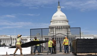 Workers remove the fence surrounding the U.S. Capitol building, six months after it was erected following the Jan. 6 riot at the Capitol, on Saturday, July 10, 2021, in Washington. (AP Photo/Jose Luis Magana)