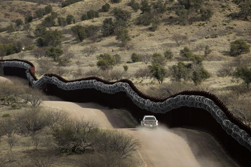 In this March 2, 2019, file photo, a Customs and Border Control agent patrols on the U.S. side of a razor-wire-covered border wall along the Mexico east of Nogales, Ariz. (AP Photo/Charlie Riedel, File)