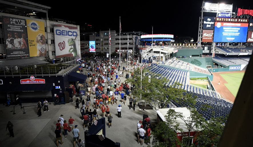 Spectators leave the stadium in the sixth inning of a baseball game between the Washington Nationals and the San Diego Padres, Saturday, July 17, 2021, in Washington. The game was suspended in the sixth inning after police said there was a shooting outside Nationals Park. (AP Photo/Nick Wass)